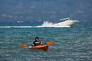 man paddle in kayak boat on calm blue water of Lake Tahoe, from Kiva Beach, California