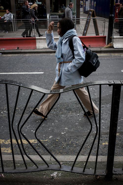 Woman pedestrian walks past bent railings in a London street.