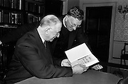 """21/5/1965<br /> 5/21/1965<br /> 21/5/1965<br /> <br /> President de Valera recived an inscribed mathematic textbook """"Matamatic na h'ard Teistimeireachta"""" from the author An Br. Tomás Ó Catnain, Mount Sion Waterford.<br /> <br /> President de Valera receiving the book from An Br. Tomás Ó Catnain"""