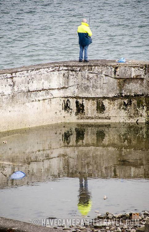 A man, with his reflection, fishes in Beaumaris on the island of Anglesey of the north coast of Wales, UK.