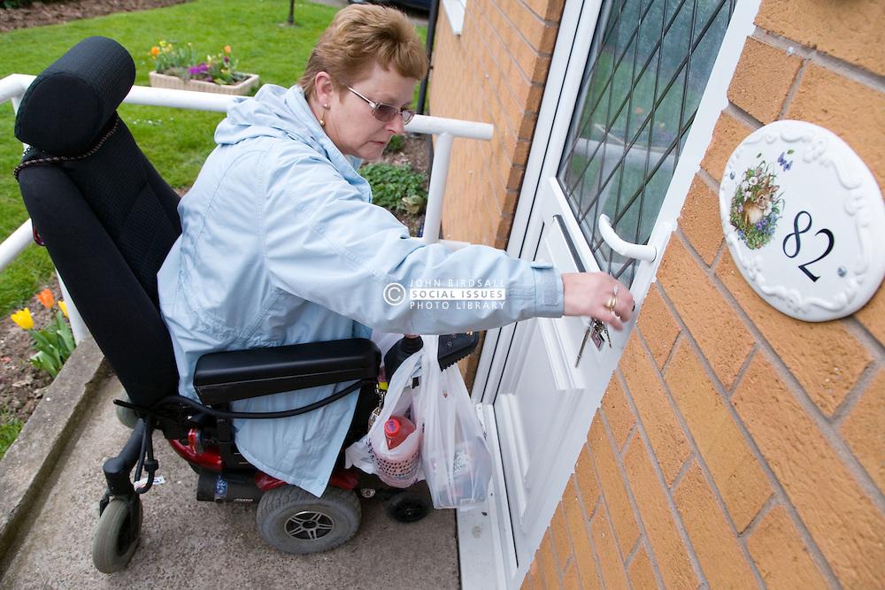 Older woman wheelchair user unlocking her front door,