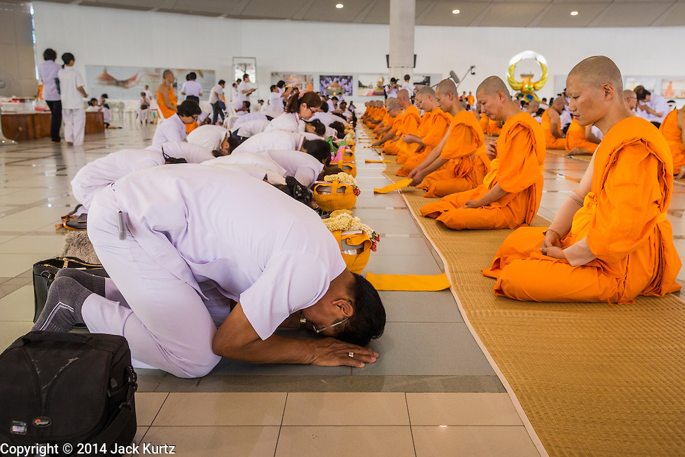 19 JULY 2014 - KHLONG LUANG, PATHUM THANI, THAILAND:  Family members pray before men newly ordained as monks and novices at Wat Phra Dhammakaya. Seventy-seven men from 18 countries were ordained as Buddhist monks and novices at Wat Phra Dhammakaya, a Buddhist temple  north of Bangkok, Saturday. It is the center of the Dhammakaya Movement, a Buddhist sect founded in the 1970s and led by Phra Dhammachayo (Phrathepyanmahamuni). It is the largest temple in Thailand. The Dhammakaya sect has an active outreach program that attracts visitors from around the world.   PHOTO BY JACK KURTZ