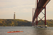 Rowing boat on Tagus river in Lisbon, with Cristo-Rei (King Christ) monument and 25th of April bridge in the background.