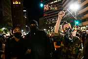 """OAKLAND, CA - JUNE 03: Demonstrators attend a """"Sit Out the Curfew"""" protest against the death of George Floyd who died on May 25 in Minneapolis whilst in police custody, along a street in Oakland, California on June 3, 2020. - US protesters welcomed new charges against Minneapolis officers in the killing of African-American man George Floyd -- but thousands still marched in cities across the country for a ninth straight night, chanting against racism and police brutality. (Photo by Philip Pacheco/Agence-France Presse/AFP)"""