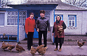 A Ukrainian farming family at home and their chickens, outside Kiev.