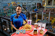 Tiffany Whitehead, a student and part-time ride supervisor at the Mall of America amusement park, with her typical day's worth of food in Bloomington, Minnesota. (From the book What I Eat: Around the World in 80 Diets.) The caloric value of her day's worth of food on a day in June was 1900 kcals. She is 21 years old; 5 feet, 7 inches tall; and 130 pounds. The Mall of America is the largest among some 50,000 shopping malls in the United States. In addition to a huge amusement park, it houses over 500 stores, 26 fast-food outlets, 37 specialty food stores, and 19 sit-down restaurants, and employs more than 11,000 year-round employees. In excess of 40 million people visit the mall annually, and more than half a billion have visited since it opened in 1992. Tiffany's job involves a lot of walking. Her main beat is the amusement park area, where she responds to radio calls regarding stalled rides and lost children and answers visitors' questions. MODEL RELEASED.
