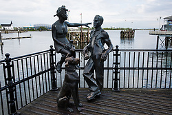 Cardiff, UK. 1st May, 2017.  A bronze sculpture of a young couple and a dog by John Clinch is pictured on Mermaid Quay with Cardiff Bay behind. The sculpture, created in 1993 and named 'People Like Us', represents the people who lived and worked in the area which was previously known as 'Tiger Bay'.