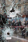 Bullet holes in windows of Casa Nostra Restaurant, Rue Fontaine au Roi, near Republique<br /><br />The Day after the terrorist jihadi attacks. Bullet holes and blood, mourning homage and cleaning up. Aftermath of deadly Paris terrorist attacks. Saturday 14th November 2015<br /> <br /> Eight terrorists dead and some 128 people killed at Stade de France, Bataclan concert Hall, Belle Equipe Restaiurant, Rue Fontaine au Roi, Two hundred people have been injured, 80 of them seriously.