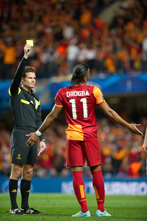 Galatasaray's Didier Drogba is shown a yellow card by Referee Felix Brych <br /> <br /> Photo by Ashley Western/CameraSport<br /> <br /> Football - UEFA Champions League First Knockout Round 2nd Leg - Chelsea v Galatasaray - Tuesday 18th March 2014 - Stamford Bridge - London<br />  <br /> © CameraSport - 43 Linden Ave. Countesthorpe. Leicester. England. LE8 5PG - Tel: +44 (0) 116 277 4147 - admin@camerasport.com - www.camerasport.com