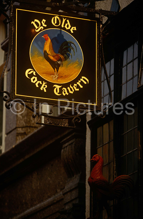 High above the streets of London's Holborn, we see the sign for the Olde Cock Tavern, one of the city's old inns from the 16th century. Ye Olde Cock Tavern is a public house on London's Fleet Street. Originally built before the 17th century, it was rebuilt, including the interior (which is thought to include work by carver Grinling Gibbons) on the other side of the road in the 1880s when a branch of the Bank of England was built where it stood. However, in the 1990s a fire broke out and destroyed many of the original ornaments, and the building has since gone through a restoration using photographs. It has been frequented by Samuel Pepys, Alfred Tennyson and Charles Dickens