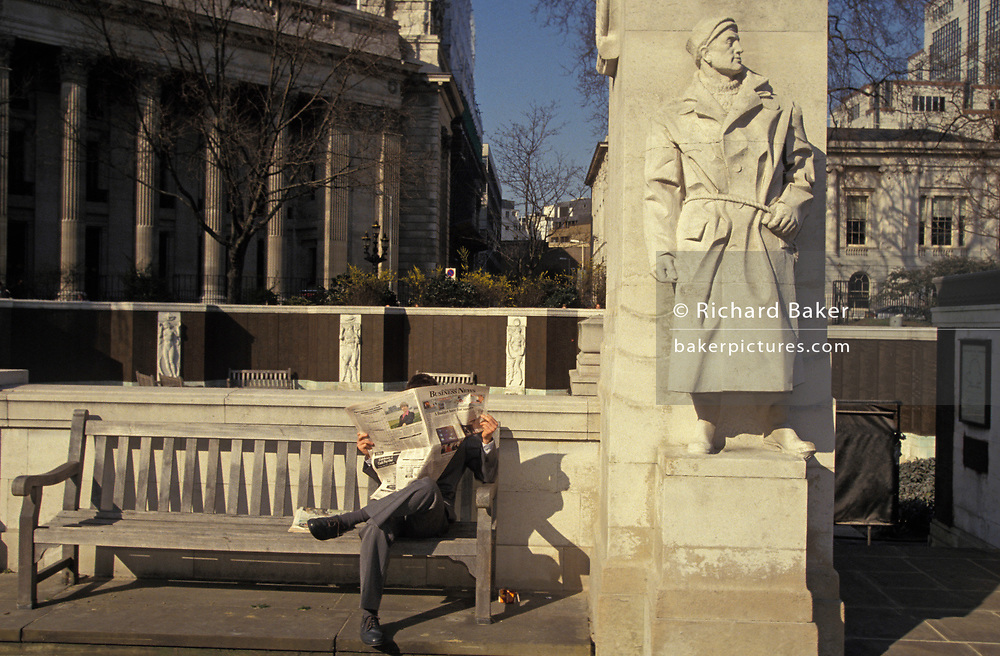 A City worker reads a newspaper alongside a figure at the memorial that commemorates civilian merchant sailors and fishermen who were killed as a result of enemy action and have no known grave in WW2, on 16th June 1994, in Trinity Square, City of London, England.