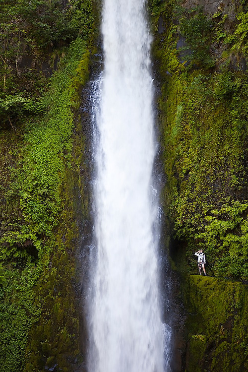 A hiker poses for a friend besides Tunnel Falls on the Eagle Creek Trail, cut into the basalt cliff behind the waterfall, in Columbia River Gorge National Scenic Area, Oregon.