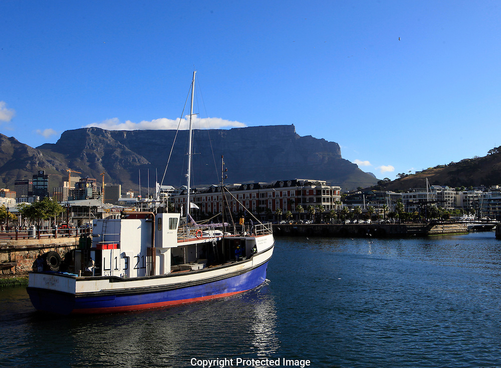 A fishing boat returns to the Harbour area of Cape Town South Africa, In the background is Table Mountain. Photo by Dennis Brack...