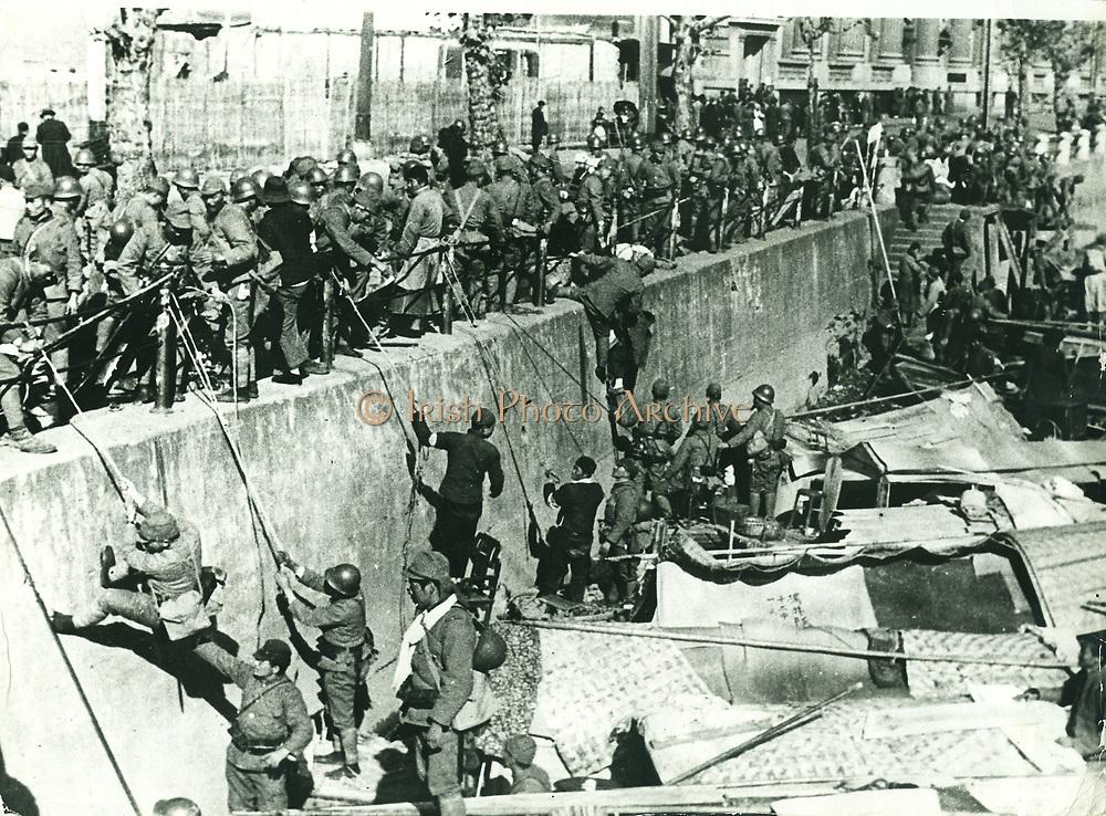 Sino-Japanese War, 1937: Japanese troops landing in the Hongkew district of Shanghai clambering up the harbour wall in Soochow C reek.