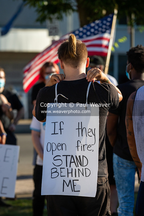 """A protester at a Black Lives Matter event in Lock Haven, Pennsylvania wears a sign reading """"if the open fire stand behind me."""""""
