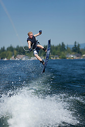 United States, Washington, Lake Sawyer, teenage boy wakeboarding in lake.  MR