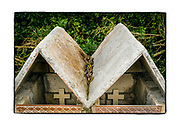 SHOT 2/13/19 3:51:20 PM - Crosses peek out from inside a pair of simple roadside capillas along Highway 109 near Francisco Uh May, Mexico in that state of Quintana Roo. Capillas, or tiny chapels, are common along the roads and highways as well as in town all over Mexico, which is largely Catholic. The capillas are often dedicated to certain patron saints or someone that has died at or near the site. Often times they contain prayer candles, pictures, personal artifacts or notes. (Photo by Marc Piscotty / © 2019)