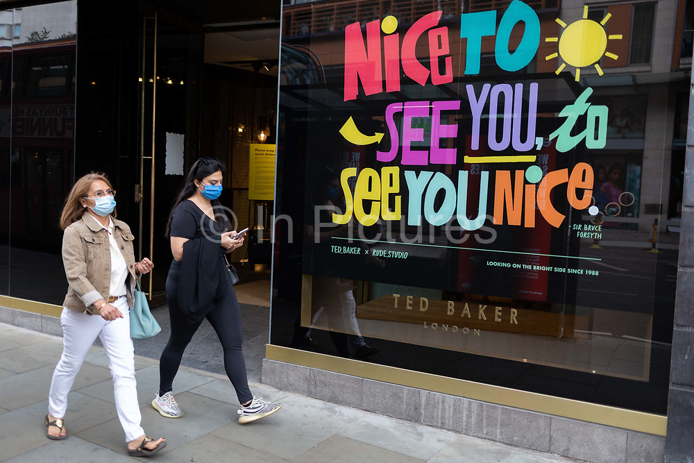 On the day that covid pandemic guidelines for shoppers in England mean that the wearing of face coverings in shops is mandatory, two women wearing face masks walk past the Knightsbridge branch of Ted Baker which is welcoming back business after lockdown, on 24th July 2020, in London, England.