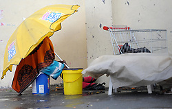 Cape Town - 180630 -This lady uses a bech umbrella for shelter while she sells her wears in Capricorn park Saturday - Photographer - Tracey Adams/African News