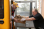 HYANNIS - Barnstable Public School food services worker Steve Kelley passes a box of meals to director Dave Badot, left, on Monday, March 23, 2020. The staff have been bagging breakfast and lunch for students on the free and reduced meal plan and then delivering them to various pick up sites.