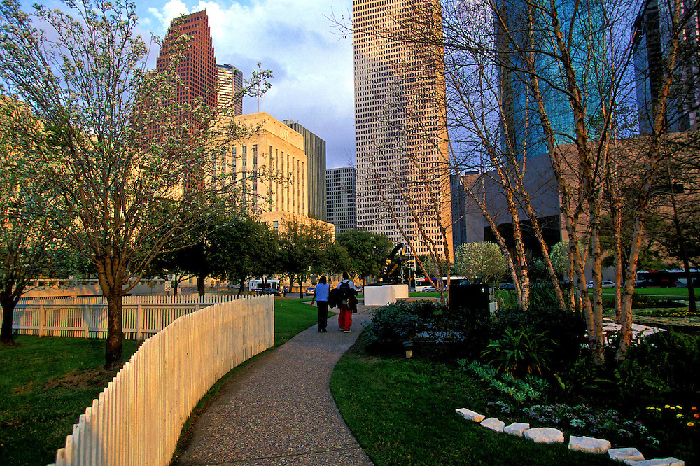 People walking on path in downtown Houston, Texas with the skyline in the background.