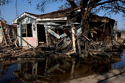 30 Sept, 2005.  New Orleans, Louisiana. Lower 9th ward. Hurricane Katrina aftermath. <br /> The remnants of the lives of ordinary folks, now covered in mud as the flood waters remain. A house washed from it's base came to rest when it smashed into a tree.<br /> Photo; ©Charlie Varley/varleypix.com