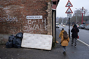 Family pass an old mattress is dumped on the street leaning against a brick wall in Balsall Heath on 18th January 2020 in Birmingham, United Kingdom. This sort of fly tipping is a common sight all over the city as unwanted or rubbish items are thrown away in public. Left for the council to clear up.