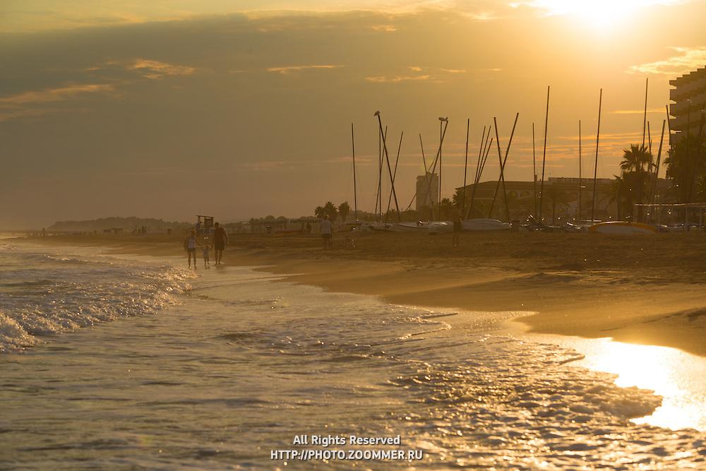 Family walk along the shore line in Costa Daurada, Spain