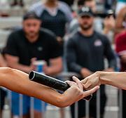 Elon University senior Lauren Brzozowski grabs a baton from graduate student Natacha Savioz during the Phoenix Invitational women's 4x400-meter relay at Erwin Belt track on May 4, 2019. The team set a new school record with a time of 3:43.14.