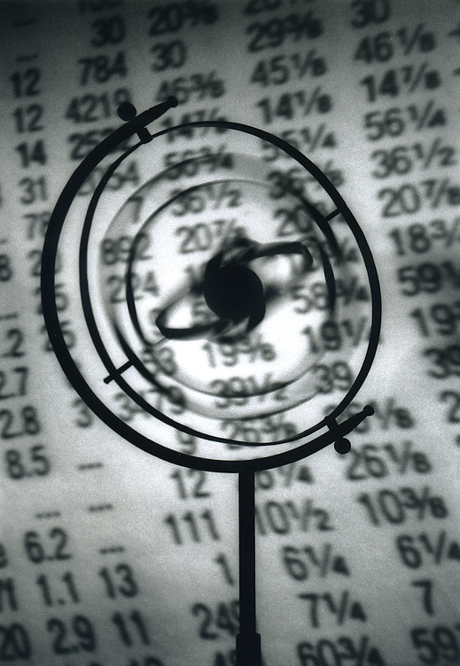 Spinning globe sculpture spins in front of financial figures from a newspaper.
