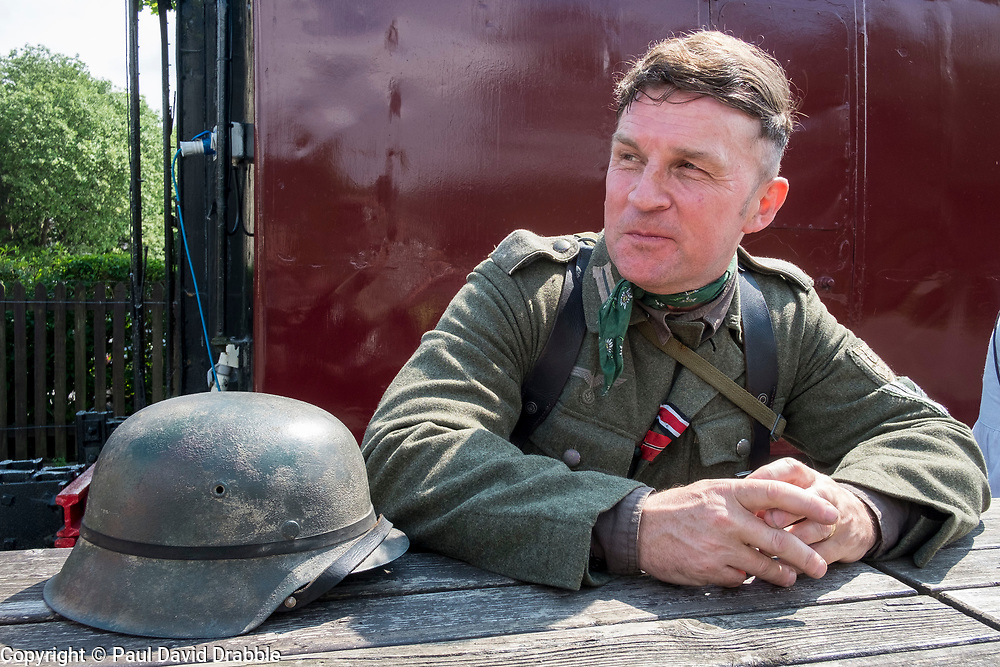 A reenactor portraying a soldier of the German Wehrmacht rests on the station platform with his M42 Steel helmet (Stahlhelm) beside him during the East Lancashire Railway 1940's Weekend Saturday 27th, Sunday 28th and  Monday 29th May 2017<br /> He is wearing the Iron Cross second class (EK2) and Eastern Front Medal (Ostmedaille) ribbons on his tunic<br /> <br />  Copyright Paul David Drabble<br />  www.pauldaviddrabble.co.uk