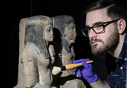 An exhibition at the National Museum of Scotland tells the story of one ancient Egyptian tomb across 1,000 years of use. Built around 1290 BC, the tomb was reused a number of times before being sealed in the 1st Century AD and left undisturbed until its excavation in the 19th Century<br /> <br /> Pictured: Dr Dan Potter, Assistant Curator with sandstone sculpture of Chief of Police and his wife.