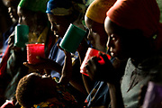 (from center to left) Bonane, Maombi, and Mbarabukeye, all victims of sexual violence, drink warm milk inside Kichanga transit center before heading to their villages in Kichanga and Nyanzale villages. Bonane lives in Kichanga center, however, Maombi and Mbarabukeye lived in a faraway village which could take up to five hours on foot. The region was so volatile and rough, the jeep could not access.