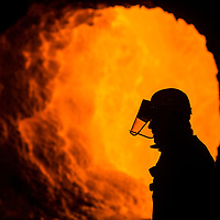 Tata Steel Scunthorpe - Heavy End - Steel Production - steel worker silhouetted against orange  glowing hot furnace