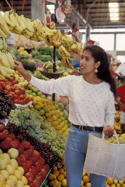 Young Hispanic middle-class woman shopping for fruit and vegetables at indoor market in San Miguel del Allende, Mexico.  Model Release.<br /> ©Bob Daemmrich