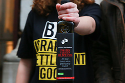 "London, UK. 3rd December, 2018. Andy Slaughter, Labour MP for Hammersmith, joins an Amnesty UK campaigner in taking a Christmas hamper of ""Israeli stolen goods"" including red wine, olive oil, honey, mineral water, eggs, dates, peppers, oranges and avocados to the Foreign Office to draw attention to the fact that these goods are all currently being produced in Israel's unlawful settlements in the occupied Palestinian West Bank and to call on governments around the world to ban the importation of Israeli settlement goods. All countries have a clear obligation to ensure respect for international humanitarian law and shouldn't recognise or assist the illegal situation that Israel's settlement policy has created."