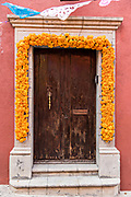 A doorway to a house decorated with marigold flowers to welcome the dead home during the Dia de Muertos festival in San Miguel de Allende, Mexico. The multi-day festival is to remember friends and family members who have died using calaveras, aztec marigolds, alfeniques, papel picado and the favorite foods and beverages of the departed.