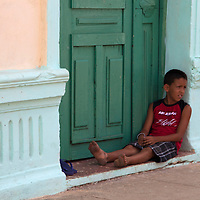 Central America, Cuba, Remedios. Cuban boy relaxing in doorway.