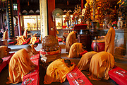 Buddhist monks in ochre yellow robes during one of their daily prayer sessions at Longhua Temple in the south of Shanghai. This is a working temple where public come to burn incense, offer gifts and to eat. Located on Longhua Road, the temple was first built in 242 AD, during the period of the Three Kingdoms. This is the oldest temple in Shanghai and also the largest at 20,000 square metres including it's grounds. Because of several destructions by the wars, most of the buildings in Longhua Temple were reconstructed during the reign of the Emperor Tongzhi and Guangxu during the Qing Dynasty.