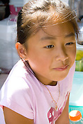 Thoughtful young SE Asian Hmong girl age 9. Hmong Sports Festival McMurray Field St Paul Minnesota USA