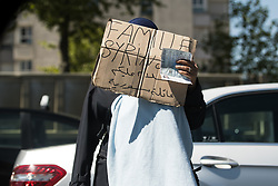 "© Licensed to London News Pictures . 09/05/2017. Paris, France . A woman , begging at the side of the road , holds a cardboard sign over her face that reads "" Syrian Family "" next to the scene where French police have cleared approximately 1000 people from an ad hoc roadside camp under roadways along a central reservation , in which migrants were living , in Porte de la Chapelle in North Paris , this morning (9th May 2017) . Photo credit: Joel Goodman/LNP"