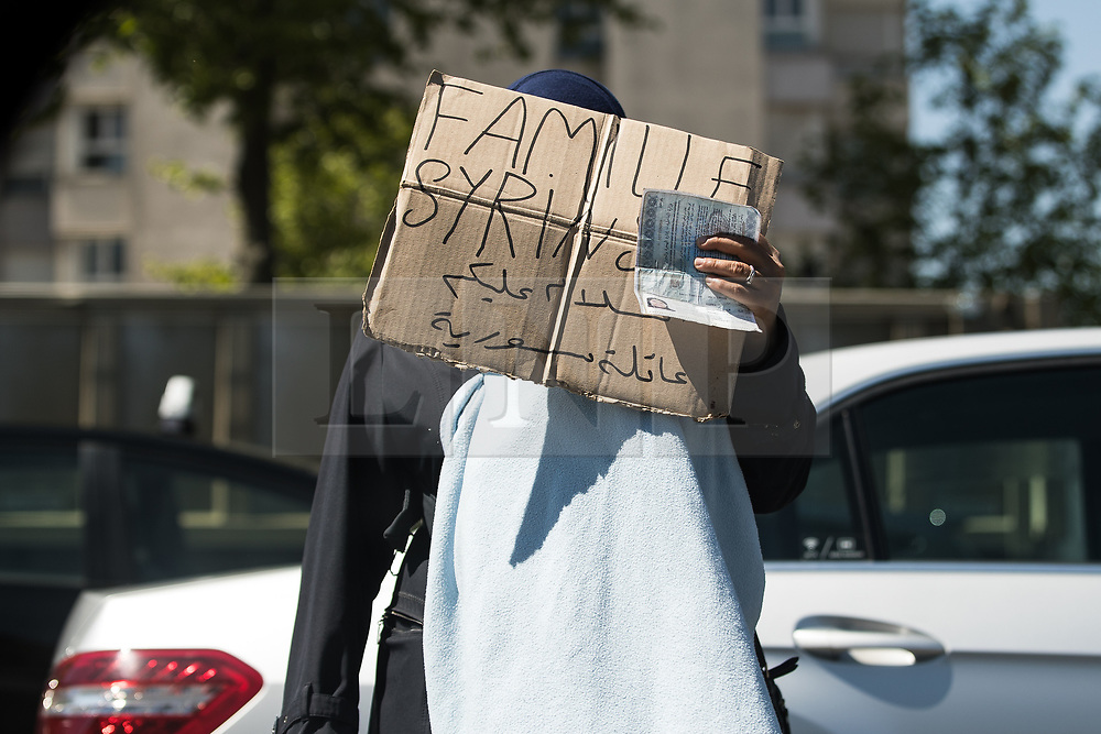 """© Licensed to London News Pictures . 09/05/2017. Paris, France . A woman , begging at the side of the road , holds a cardboard sign over her face that reads """" Syrian Family """" next to the scene where French police have cleared approximately 1000 people from an ad hoc roadside camp under roadways along a central reservation , in which migrants were living , in Porte de la Chapelle in North Paris , this morning (9th May 2017) . Photo credit: Joel Goodman/LNP"""