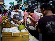 """24 JULY 2018 - BANGKOK, THAILAND: Tourists buy durian from a street vender on Khao San Road, in Bangkok. Khao San Road is Bangkok's original """"Backpacker Ghetto"""" and is still a popular hub for travelers, with an active night market and many street food stalls. The Bangkok municipal government plans to shut down the street market by early August because city officials say the venders, who set up on sidewalks and public streets, pose a threat to public safety and could impede emergency vehicles. It's the latest in a series of night markets the city has closed.    PHOTO BY JACK KURTZ"""