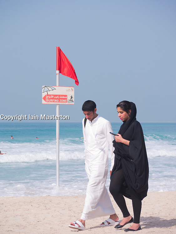 Young Arab couple walking on beach at Jumeirah in Dubai in United Arab Emirates