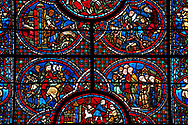 Medieval stained glass Window of the Gothic Cathedral of Chartres, France - dedicated to The life of St Lubin. Centre bottom panel - Signature panel (Wine cryers). Above left - Procession; a nobleman and his retinue, above right - Procession; a group of laymen and clerics departing from a church. Top left -  The young Lubin working as a shepherd, top right - A monk gives Lubin a belt with the alphabet written on it. A UNESCO World Heritage Site.  . .<br /> <br /> Visit our MEDIEVAL ART PHOTO COLLECTIONS for more   photos  to download or buy as prints https://funkystock.photoshelter.com/gallery-collection/Medieval-Middle-Ages-Art-Artefacts-Antiquities-Pictures-Images-of/C0000YpKXiAHnG2k