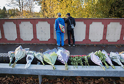 © Licensed to London News Pictures. 13/11/2016. Croydon, UK. People look at the crash site from a bridge where floral tributes have been placed. Engineers work to restore the line at the site where seven people died and 50 were injured when a tram rolled over on Wednesday 9th November. Photo credit: Peter Macdiarmid/LNP