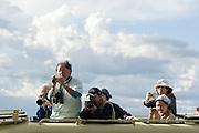 Japanese tourists taking pictures from roof of safari vehicle. Masai Mara, Kenya
