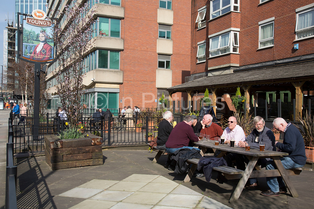 Group of older men sitting outside a pub drinking their pints in the sunshine in Southwark, London, UK.