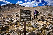 Bishop Pass trail entrance sign and backpacker, Kings Canyon National Park, California USA