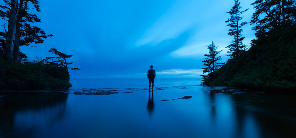 Zach Podell-Eberhardt looks out over the Pacific Ocean from the top of Tsusiat Falls, West Coast Trail, British Columbia, Canada.